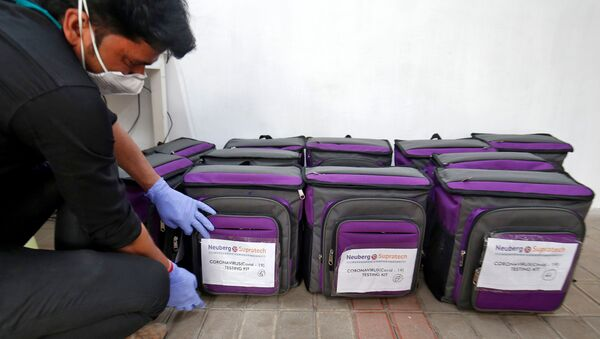 A laboratory technician places a tag on a box containing coronavirus disease (COVID-19) testing kit at a sample collection centre in Ahmedabad, India March 26, 2020. - Sputnik International