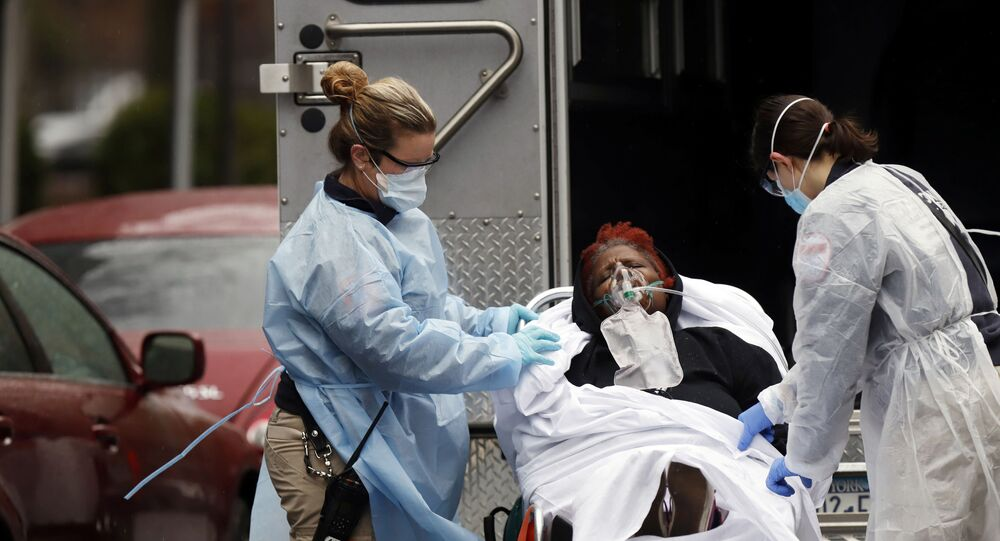 Emergency Medical Technicians (EMT) wearing protective gears wheel a sick patient to a waiting ambulance during the outbreak of coronavirus disease (COVID-19) in New York City, New York, U.S.