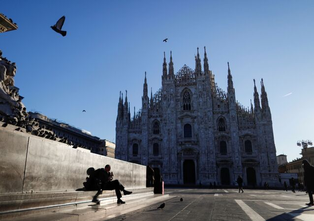 People walk through a near-empty Duomo square, usually full of people, as a coronavirus outbreak in northern Italy continues to grow, in Milan, Italy February 28, 2020.