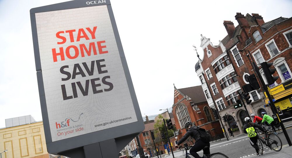 Cyclists pass an electronic billboard displaying a Public health information campaign message from the UK government and local government in London as the spread of the coronavirus disease (COVID-19) continues, London, Britain, March 28, 2020.