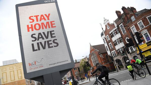 Cyclists pass an electronic billboard displaying a Public health information campaign message from the UK government and local government in London as the spread of the coronavirus disease (COVID-19) continues, London, Britain, March 28, 2020. - Sputnik International
