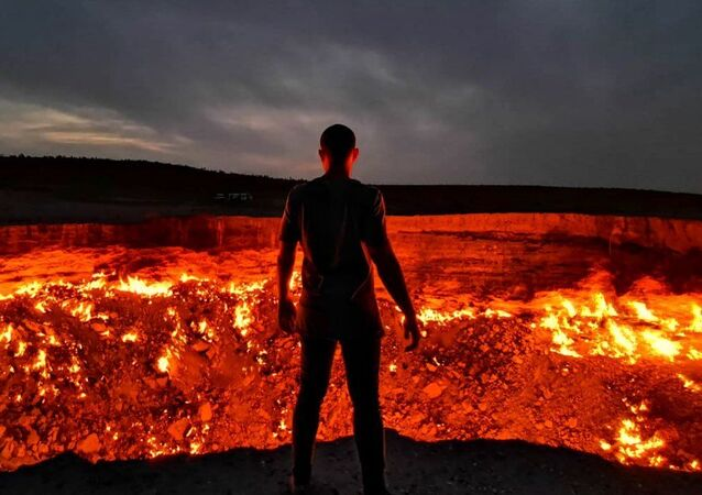 Man Stands in Front of Darvaza Crater in Turkmenistan