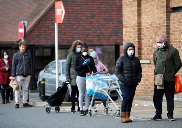 People wearing protective facemasks queue outside Sainsbury's supermarket in Streatham