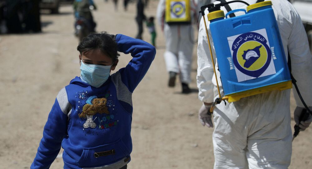 Syrian girl wears a face mask as members of the Syrian Civil defence sanitize the Bab Al-Nour