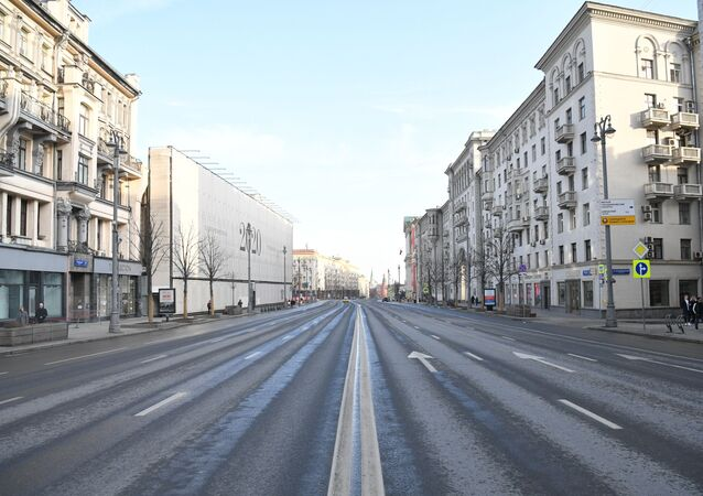 People walk along a deserted street with closed shops, in Moscow, Russia.