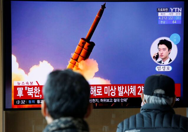 People watch a TV showing a file picture for a news report on North Korea firing two unidentified projectiles, in Seoul, South Korea, March 2, 2020.