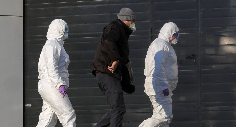 Medical staff members wearing protective suits accompany a man at a hospital, where coronavirus disease (COVID-19) patients are being treated, in Moscow, Russia March 17, 2020