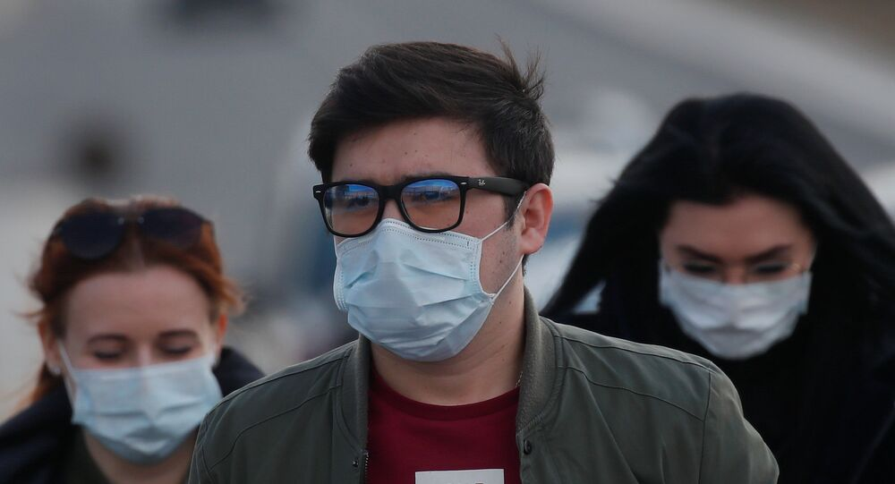People wearing protective masks walk near a hospital for patients infected with coronavirus disease (COVID-19) on the outskirts of Moscow, Russia March 23, 2020.