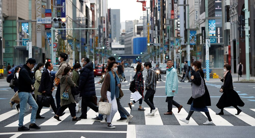 Passersby wearing protective face masks, following an outbreak of the coronavirus disease (COVID-19), are seen at Ginza shopping district during the first weekend after Tokyo Governor Yuriko Koike (not pictured) urged Tokyo residents to stay indoors in a bid to keep a coronavirus from spreading, in Tokyo, Japan March 28, 2020.