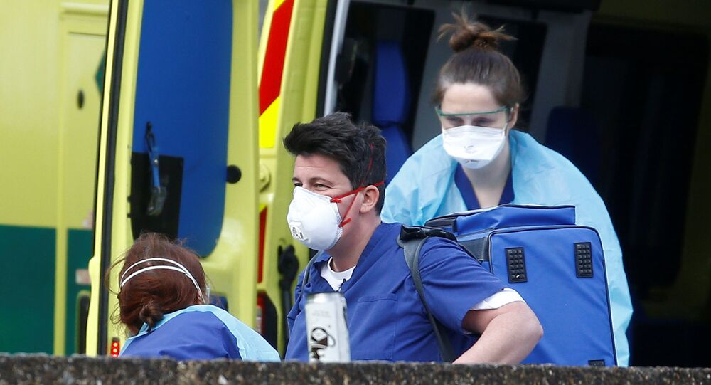 Medical staff wearing protective masks and clothing in a Ambulance outside St Thomas' hospital, as the spread of the coronavirus disease (COVID-19) continues, London, Britain, March 29, 2020.