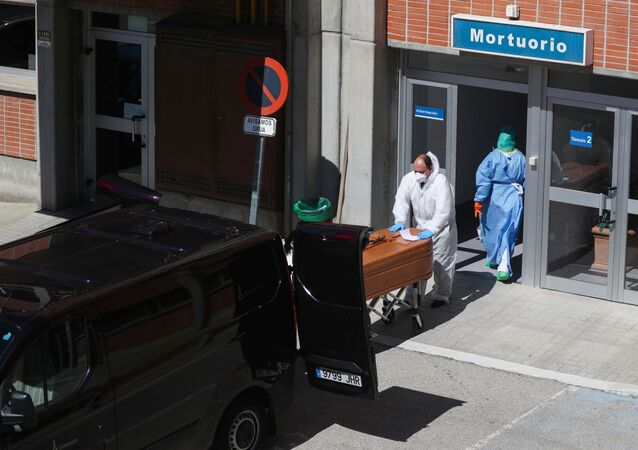 A funeral worker wearing a protective suit carries a coffin out of the morgue at Severo Ochoa Hospital, during the coronavirus disease (COVID-19) outbreak in Leganes, Spain, March 26, 2020