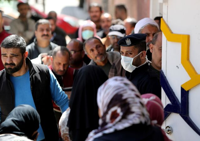 A policeman, wearing a mask as a precaution against the the coronavirus disease (COVID-19), stands guard as Palestinians wait outside a bank to withdraw cash, in Gaza City 29 March 2020.