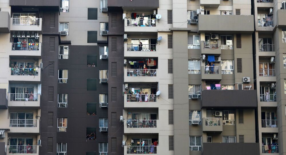Residents clap and bang utensils from their balconies to cheer for emergency personnel and sanitation workers who are on the frontlines in the fight against coronavirus, in Noida, India, March 22, 2020