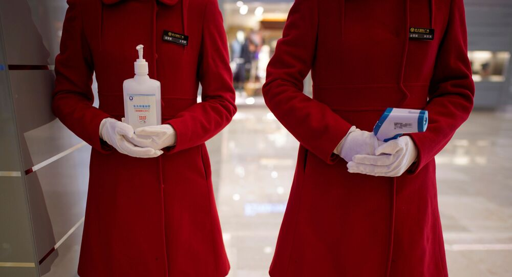 Staff members holding disinfectant gel and thermometer stand at an entrance of a shopping mall in Wuhan, Hubei province, the epicentre of China's coronavirus disease (COVID-19) outbreak, March 30, 2020.