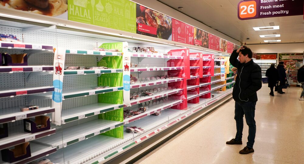 A man stands next to shelves empty of fresh meat in a supermarket, as the number of worldwide coronavirus cases continues to grow,  in London, Britain, 15 March 2020.