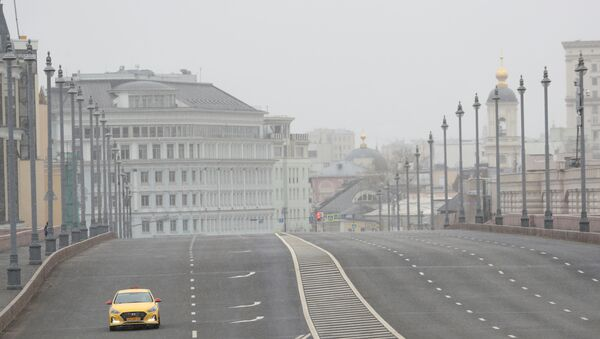 A car drives along a bridge across the Moskva River, after the city authorities announced a partial lockdown ordering residents to stay at home to prevent the spread of coronavirus disease (COVID-19), in central Moscow, Russia March 30, 2020 - Sputnik International
