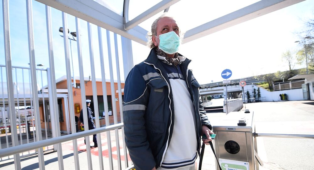 Fiat Chrysler Automobiles (FCA) worker, wearing a protective face mask, leaves a Mirafiori plant, after the Italian government puts the whole country on lockdown as new coronavirus cases surge, in Turin, Italy March 10, 2020