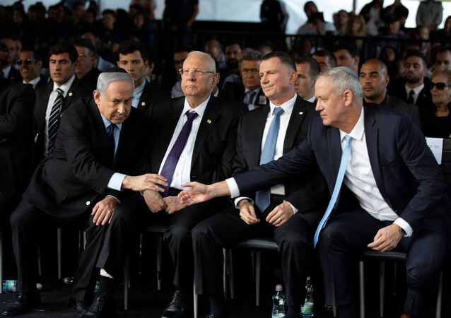 Head of Israel's Blue and White Party Benny Gantz and Israeli Prime Minister Benjamin Netanyahu shake hands as they attend a memorial ceremony for the late prime minister Yitzhak Rabin at Mount Herzl military cemetery in Jerusalem as Israel marks the 24th anniversary of Rabin's killing by an ultra-nationalist Jewish assassin, November 10, 2019