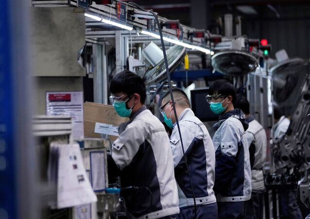 Employees wearing face masks work on a car seat assembly line at Yanfeng Adient factory in Shanghai, China, as the country is hit by an outbreak of a new coronavirus, February 24, 2020