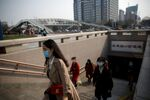 People wearing face masks exit a subway station following an outbreak of the coronavirus disease (COVID-19), in Beijing, China 30 March 2020.