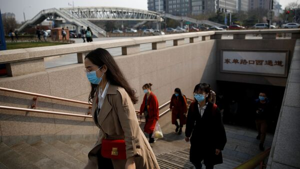 People wearing face masks exit a subway station following an outbreak of the coronavirus disease (COVID-19), in Beijing, China 30 March 2020. - Sputnik International