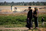 An Israeli watchtower is seen as Palestinians stand at the Israel-Gaza border fence in the southern Gaza Strip, 28 February 2020.