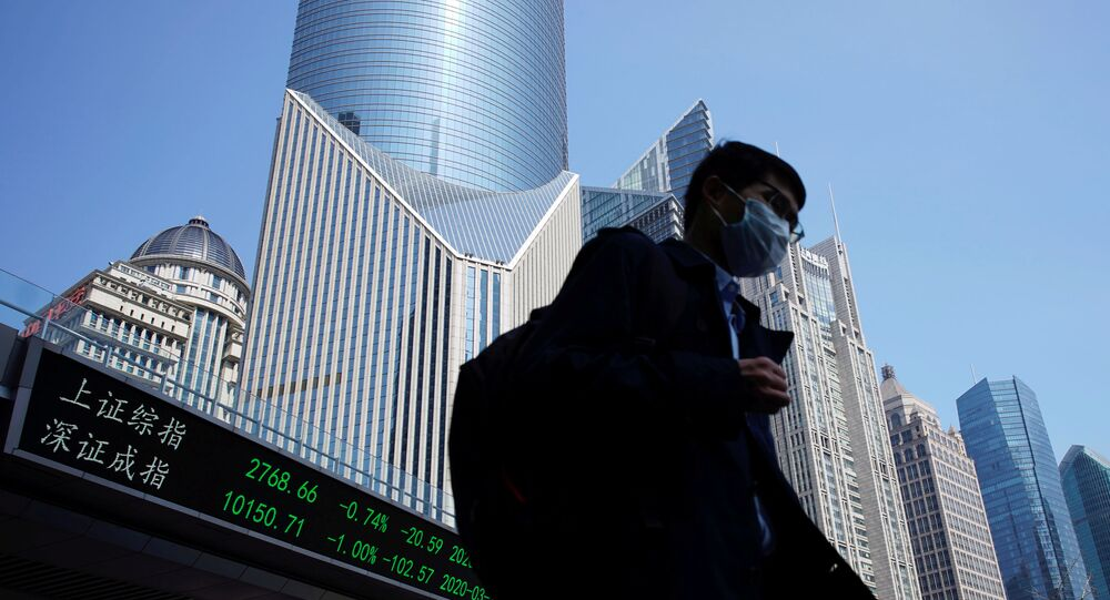 A pedestrian wearing a face mask walks near an overpass with an electronic board showing stock information, following an outbreak of the coronavirus disease (COVID-19), at Lujiazui financial district in Shanghai, China March 17, 2020.