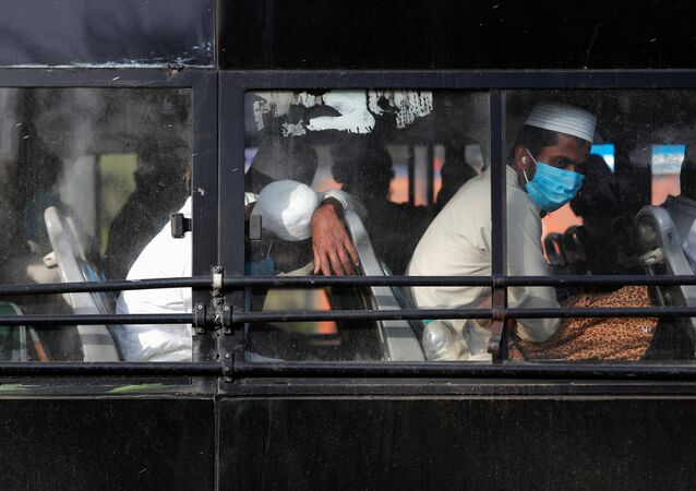 Men wearing protective masks sit inside a bus that will take them to a quarantine facility, amid concerns about the spread of coronavirus disease (COVID-19), in Nizamuddin area of New Delhi, India, March 31, 2020