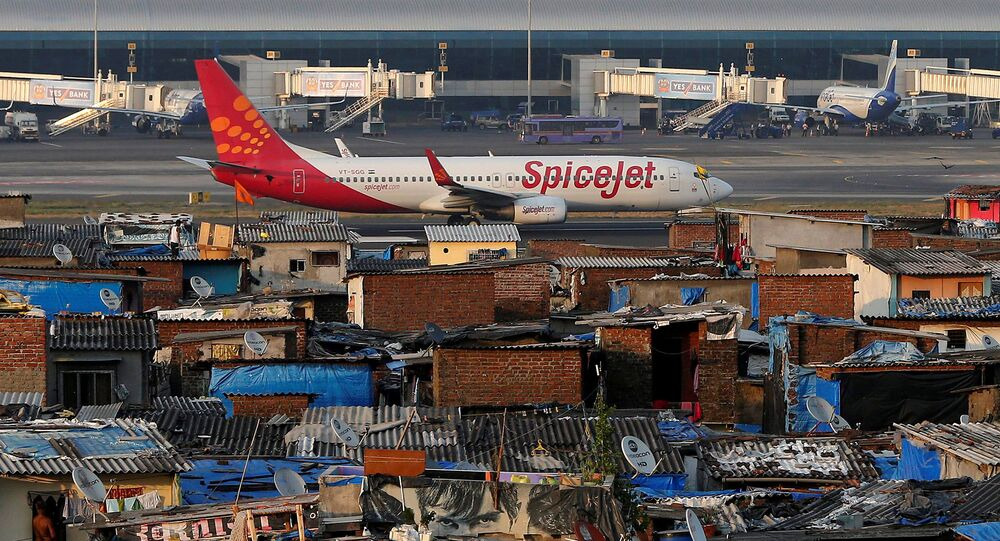 A SpiceJet passenger aircraft taxis on the runway at the airport next to a slum area in Mumbai December 19, 2014