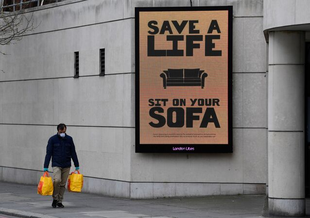 A man walks past a Public Health advertisment in London