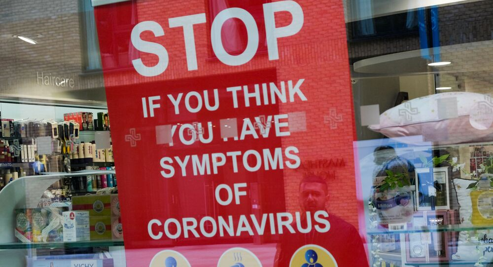 A poster in the window of a pharmacy is pictured in Royal Wharf as the spread of the coronavirus disease (COVID-19) continues, in London, Britain, March 31, 2020