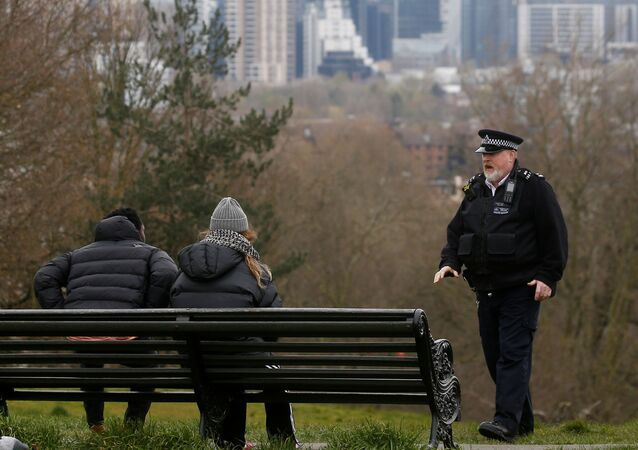 A police officer talks to people at Greenwich Park as the spread of the coronavirus disease (COVID-19) continues, London, Britain, March 31, 2020