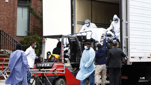 Workers load deceased person into truck trailer outside Brooklyn Hospital Center during the coronavirus disease (COVID-19) in New York - Sputnik International