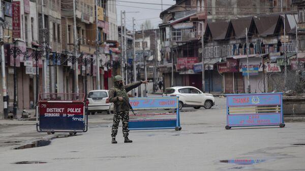 An Indian paramilitary soldier gestures towards a Kashmiri man during lockdown in Srinagar, Indian controlled Kashmir, Wednesday, March 25, 2020 - Sputnik International