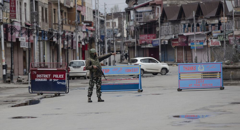 An Indian paramilitary soldier gestures towards a Kashmiri man during lockdown in Srinagar, Indian controlled Kashmir, Wednesday, March 25, 2020