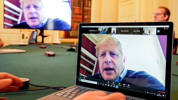 Britain's Prime Minister Boris Johnson appears on monitors for the coronavirus disease (COVID-19) meeting in London, Britain March 28, 2020. The prime minister chairs the morning update meeting on the coronavirus remotely from Number 11 Downing Street, since self-isolating after testing positive for the virus. - Sputnik International