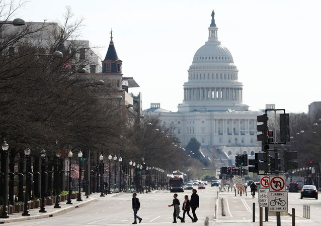 People cross Pennsylvania Avenue during a morning commuter hour, as Mayor Muriel Bowser declared a State of Emergency due to the coronavirus disease (COVID-19) in Washington, U.S., March 16, 2020