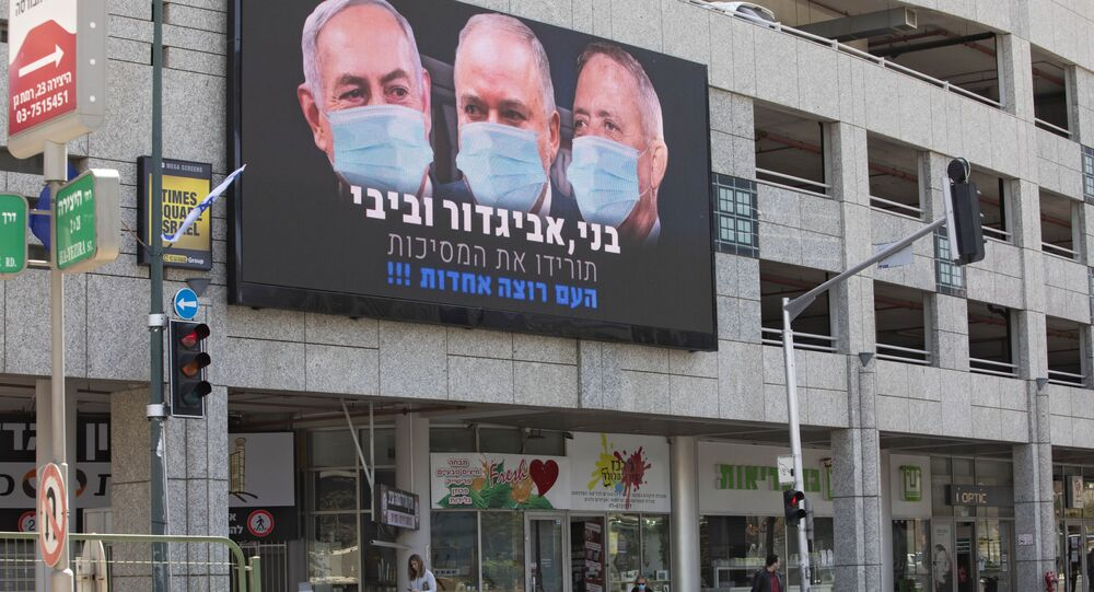A billboard shows Israeli Prime Minister Benjamin Netanyahu, left, Israeli Former Defense Minister and leader of the Yisrael Beiteinu (Israel Our Home) right-wing party Avigdor Lieberman, center, and Blue and White party leader Benny Gantz, wearing masks in the Israeli city of Ramat Gan, near Tel Aviv, Sunday, March 29, 2020.