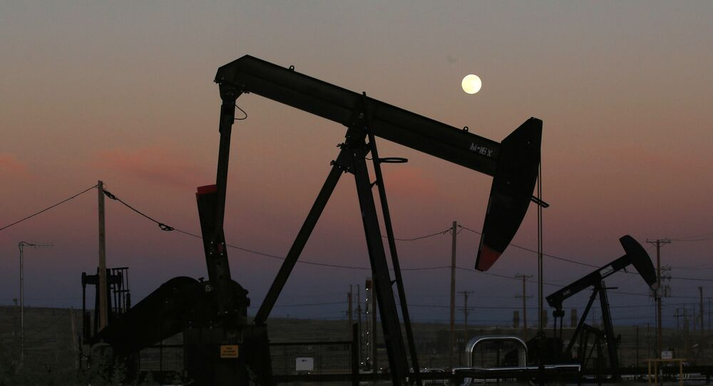 FILE - In this June 8, 2017, file photo, oil derricks are busy pumping as the moon rises near the La Paloma Generating Station in McKittrick, Calif. The U.S. is on pace to leapfrog both Saudi Arabia and Russia as the world's biggest oil producer