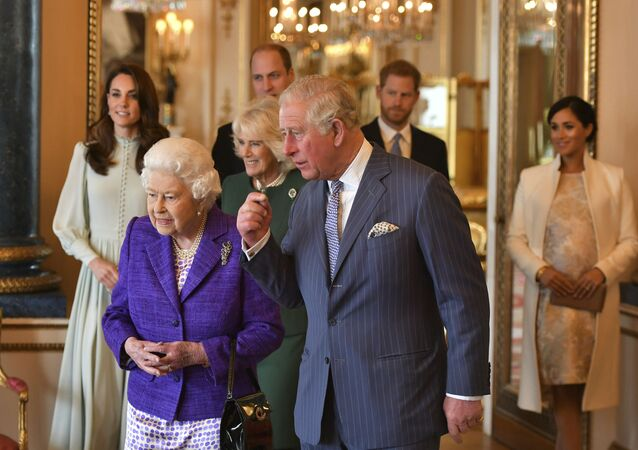 Britain's Queen Elizabeth II is joined by Prince Charles, the Prince of Wales, and at rear, from left, Kate, Duchess of Cambridge, Camilla, Duchess of Cornwall, Prince William, Prince Harry and Meghan, Duchess of Sussex during a reception at Buckingham Palace, London, Tuesday March 5, 2019, to mark the fiftieth anniversary of the investiture of the Prince of Wales