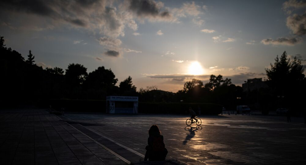 A woman sits outside the Panathenaic stadium, during a nationwide lockdown to contain the spread of the coronavirus disease (COVID-19), in Athens, Greece, 29 March 2020.