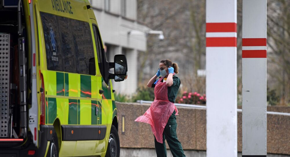 A member of staff wearing PPE of gloves, an apron and a face mask as a precautionary measure against COVID-19, prepares to disinfect an ambulance after it arrived with a patient at St Thomas' Hospital in north London, on April 1, 2020, as life in Britain continues during the nationwide lockdown to combat the novel coronavirus pandemic.