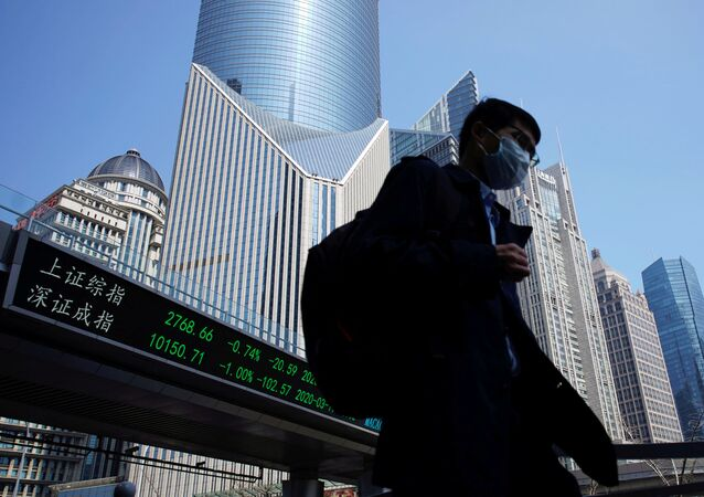 A pedestrian wearing a face mask walks near an overpass with an electronic board showing stock information, following an outbreak of the coronavirus disease (COVID-19), at Lujiazui financial district in Shanghai, China March 17, 2020