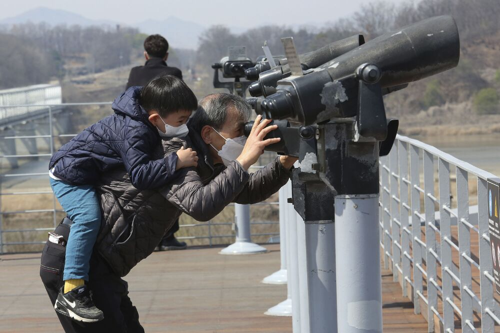 A South Korean grandfather and his grandson wearing face masks to help protect against the coronavirus use binoculars to view their northern neighbours at Imjingak in Paju, near the border with North Korea, Tuesday, 31 March 2020.