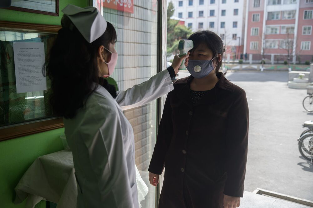 A health worker takes the temperature of a woman amid concerns over the COVID-19 coronavirus at an entrance of the Pyongchon District People's Hospital in Pyongyang on 1 April 2020.