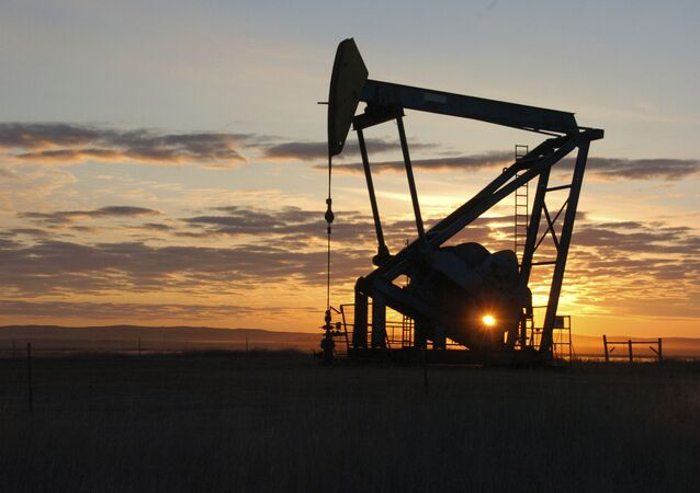 This Nov. 6, 2013 file photo shows a Whiting Petroleum Co. pump jack pulls crude oil from the Bakken region of the Northern Plains near Bainville, Mont.
