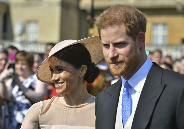 Meghan, the Duchess of Sussex walks with her husband, Prince Harry as they attend a garden party at Buckingham Palace in London, 22 May 2018