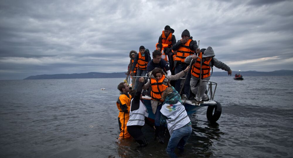 In this Thursday, Dec. 3, 2015 photo, volunteers help refugees disembark from a vessel carrying Yazidi refugee Samir Qasu, 45, from Sinjar, Iraq, and his wife Bessi, 42, their two daughters Delphine, 18, seen center left,  Dunia 13, and their two sons Dilshad, 17, seen center left, and Dildar, 10, as it arrives to the northeastern Greek island of Lesbos from the Turkish coast.