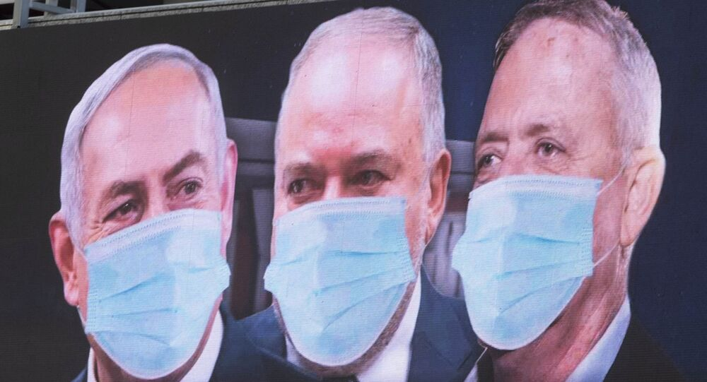 Israeli Prime Minister Benjamin Netanyahu, left, Israeli Former Defense Minister and leader of the Yisrael Beiteinu (Israel Our Home) right-wing party Avigdor Lieberman, center, and Blue and White party leader Benny Gantz, are shown on a billboard wearing masks in the Israeli city of Ramat Gan, near Tel Aviv, Sunday, March 29, 2020.