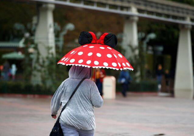 A person walks by Disneyland theme park in Anaheim, California, U.S., March 13, 2020